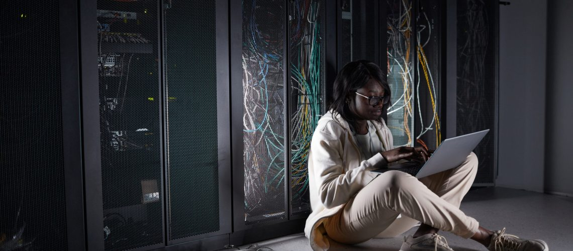 Full length portrait of young African-American woman sitting on floor in server room and using laptop while working with supercomputer at data center, copy space