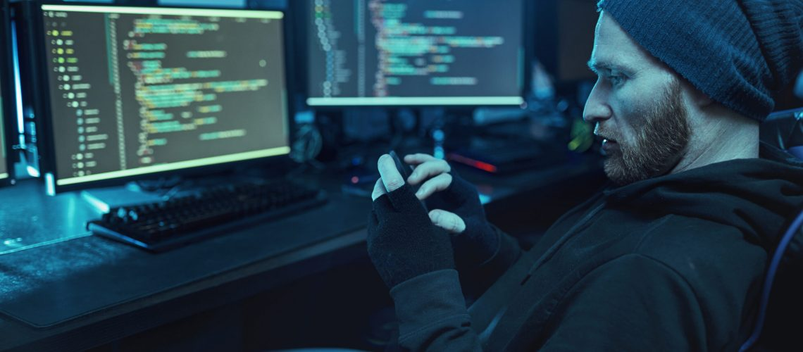 Bearded young hacker in hat and hoody shirt sitting in front of computer monitors with software and using mobile phone in dark room