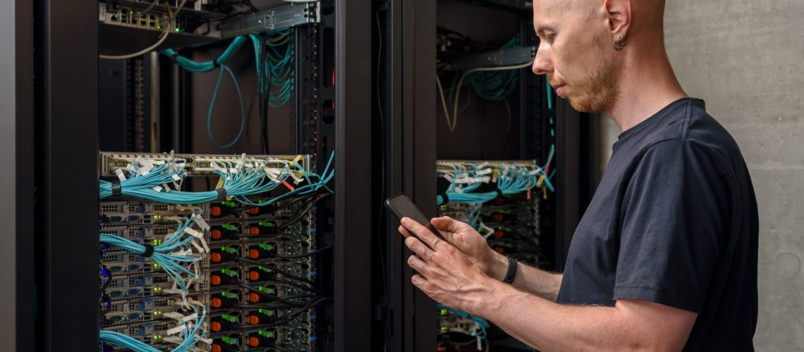Man data center technician performing server maintenance. Using mobile phone to troubleshooting