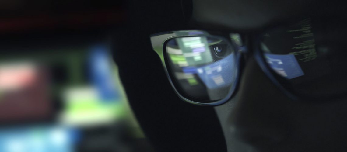 Nerd hacker with glasses working with a computer in the dark, cybersecurity concept