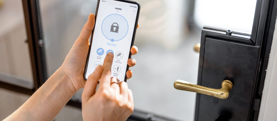 Smartphone with launched application for alarm security system, lock or unlock entrance door on interior background. Focus on mobile. Smart and safe home concept.